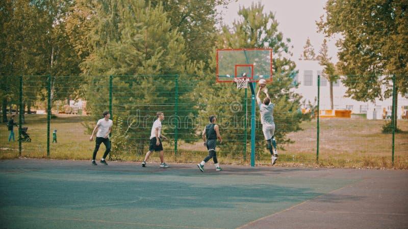 Vier junge Freunde, die Basketball auf dem Sportplatz spielen lizenzfreies stockfoto