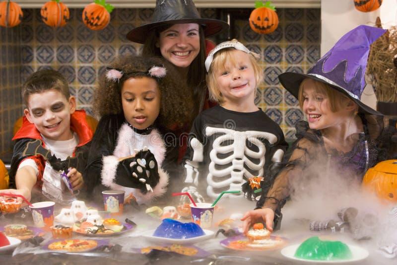 Vier junge Freunde und eine Frau bei Halloween stockbild