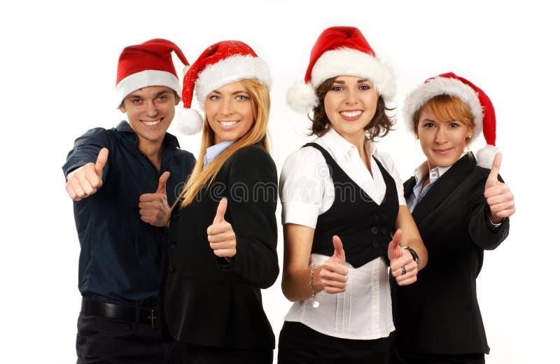 Vier junge Geschäftspersonen in den Weihnachtshüten lizenzfreie stockfotos