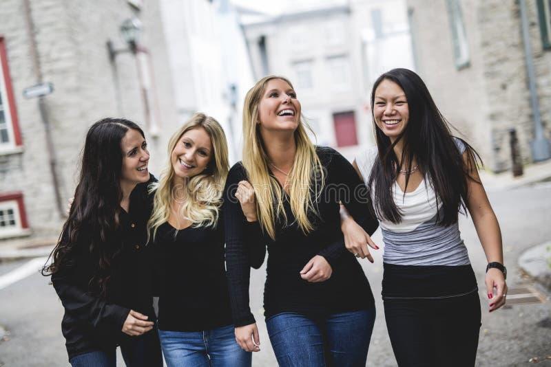 Vier junge gute Freundinleute in der Stadt lizenzfreie stockbilder