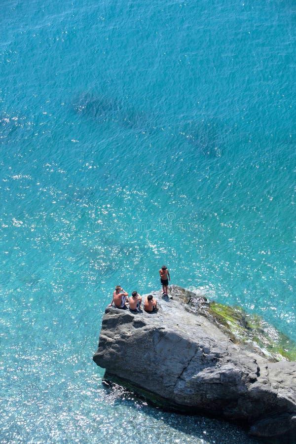 Vier junge Jungen, welche die Felsen überwachen den Tag sitzen, gehen vorbei lizenzfreie stockbilder