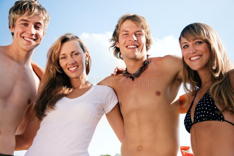 Vier junge Leute auf dem Strand lizenzfreies stockfoto