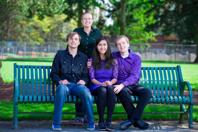 Vier junge multi ethnische Freunde zusammen am Park lizenzfreie stockfotos