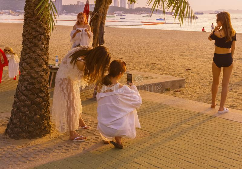 Vier, junge weibliche chinesische Touristen taten ein Bikinischießen auf dem Strand von Pattaya stockbild