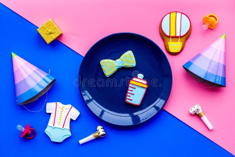 Vier kind` s verjaardag Koekjes in vorm van babytoebehoren, partijhoeden, giftdoos, confettien op roze en blauw stock foto