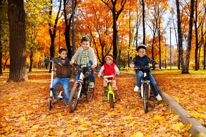Vier Kinder in den Fahrrädern stockbild