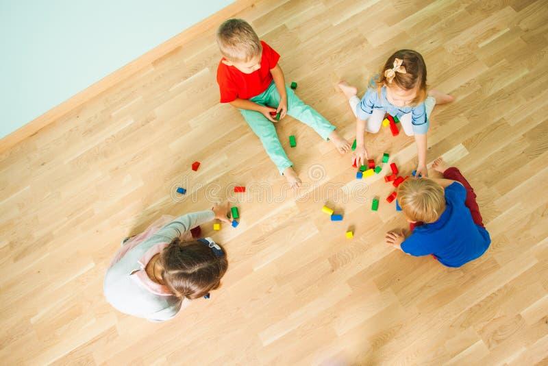 Vier Kinder, die auf dem Boden ihres Raumes spielen lizenzfreies stockfoto