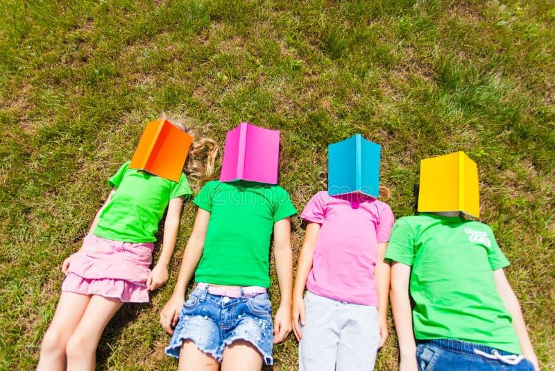 Vier Kinder, die auf einen Boden mit Büchern auf ihren Gesichtern legen stockfotos