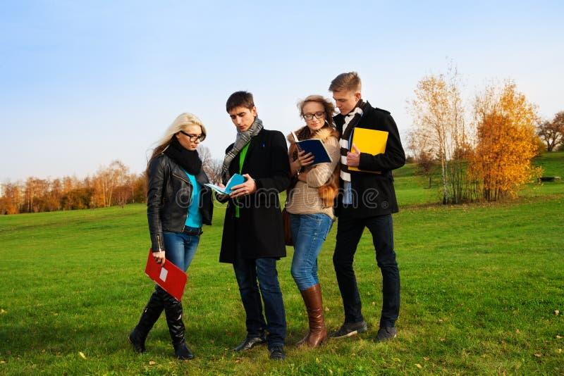 Vier Kinder, die im Park plaudern lizenzfreie stockfotos