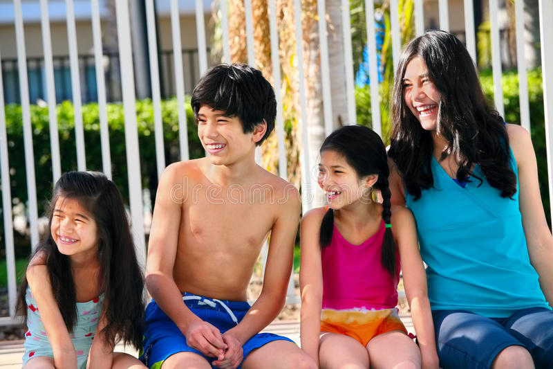 Vier Kinder durch die Poolseite stockbild