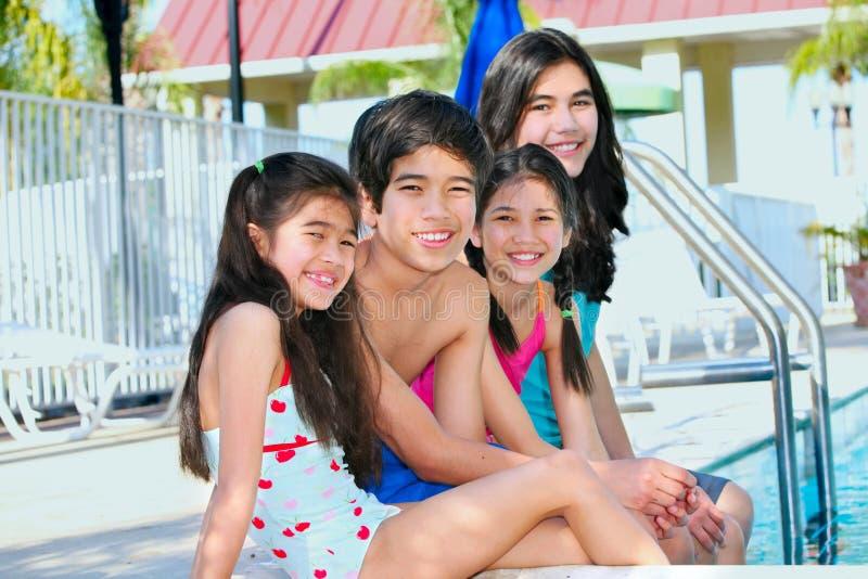 Vier Kinder durch die Poolseite stockfotos