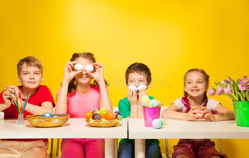 Vier Kinder sitzen am Tisch mit Ostereiern lizenzfreie stockfotos