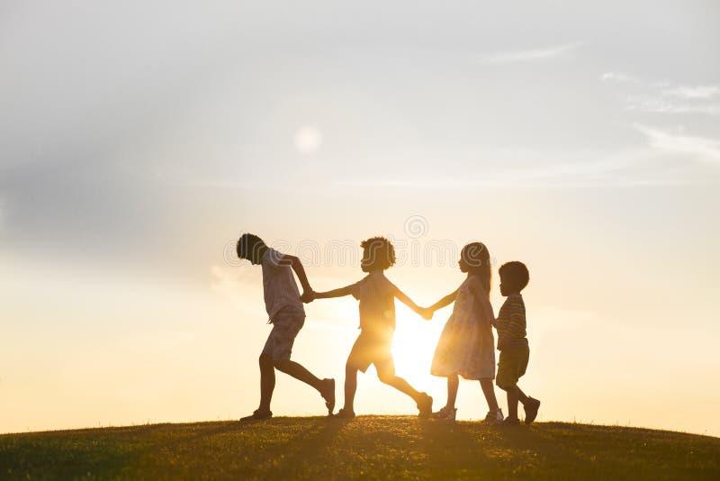 Vier Kinder spielen auf Sonnenuntergang lizenzfreies stockfoto