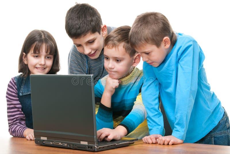 Vier kinderen die gebruikend laptop bestuderen royalty-vrije stock fotografie