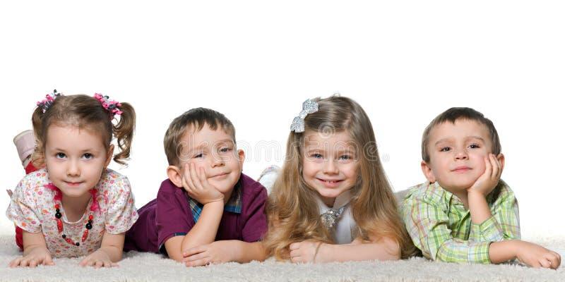 Vier kinderen die op het tapijt liggen stock foto