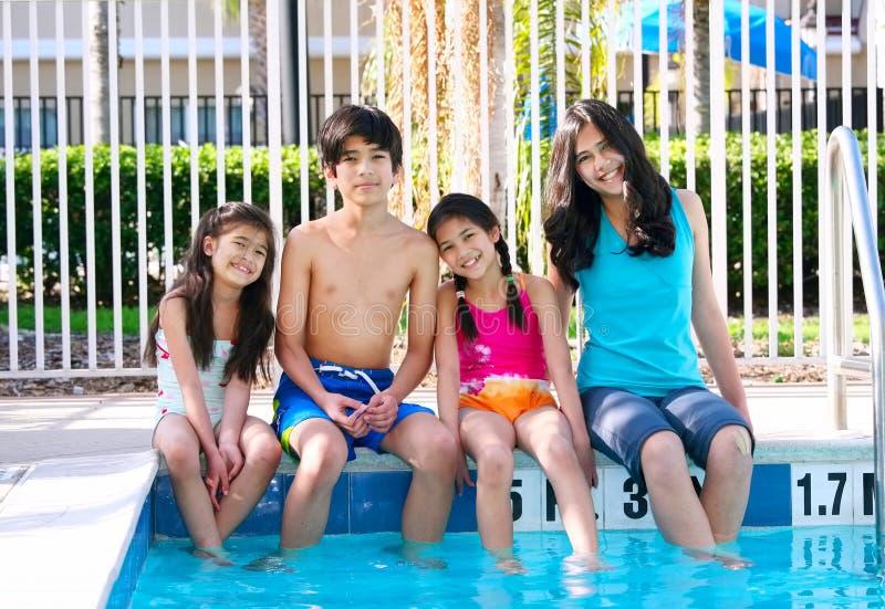 Vier kinderen door de poolkant royalty-vrije stock fotografie