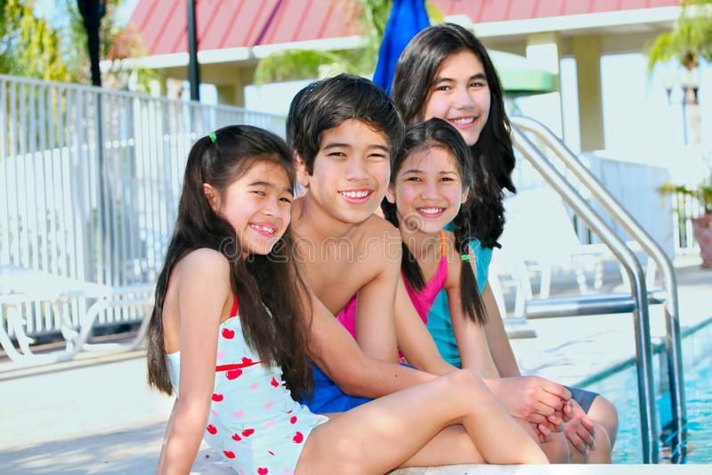 Vier kinderen door de poolkant stock foto's