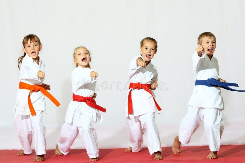 Vier kinderen in kimono raken een stempel op een witte achtergrond royalty-vrije stock foto