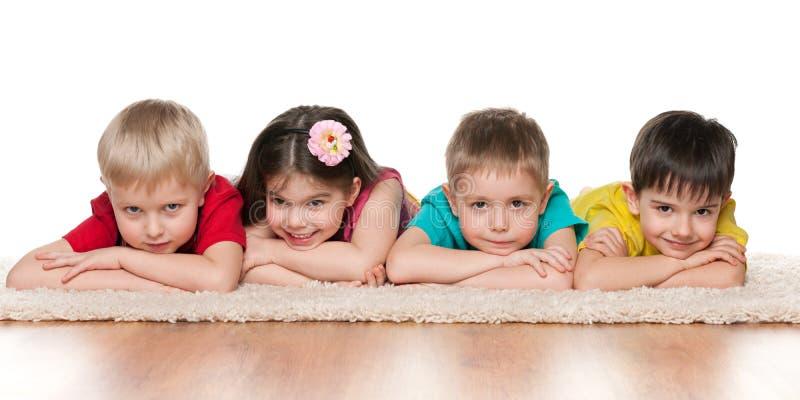 Vier kinderen op het witte tapijt royalty-vrije stock fotografie