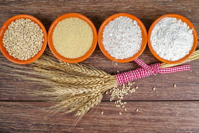 Vier kleine kommen met gehele tarwe, kouskous, geheel tarwemeel, bloem en schoof voor alle doeleinden van tarweoren stock foto