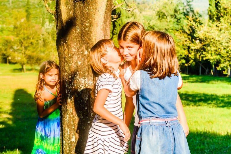 Vier kleine Mädchen, die im Park spielen und flüstern stockfotos