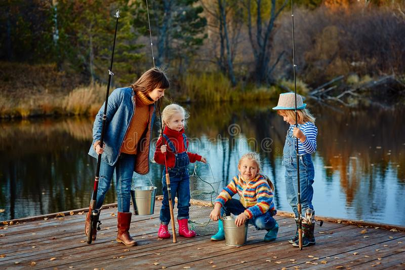 Vier kleine Mädchen fangen Fische auf einem hölzernen Ponton Wochenende am Th stockfotos