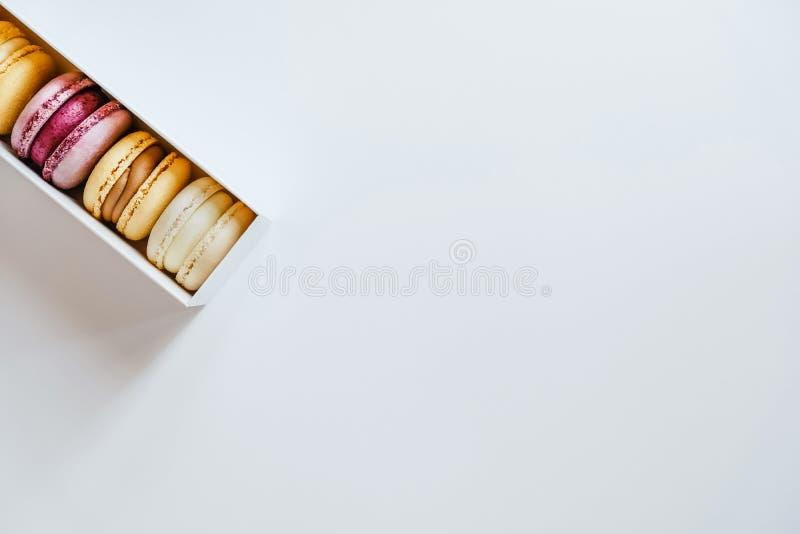 Vier kleurrijke macaroones op de witte doos stock afbeelding