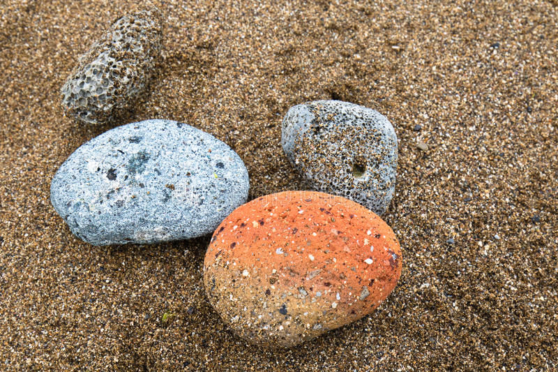 Vier kleurrijke rotsen die op zandige strandachtergrond liggen, azkorristrand, Baskisch land, Spanje royalty-vrije stock afbeeldingen
