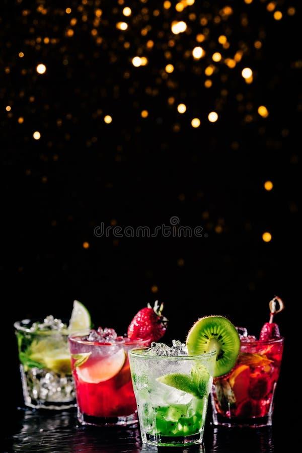 Vier kleurrijke smakelijke alcoholische cocktails op een rij bij de bartribune Feestelijke vakantie bokeh stock afbeeldingen