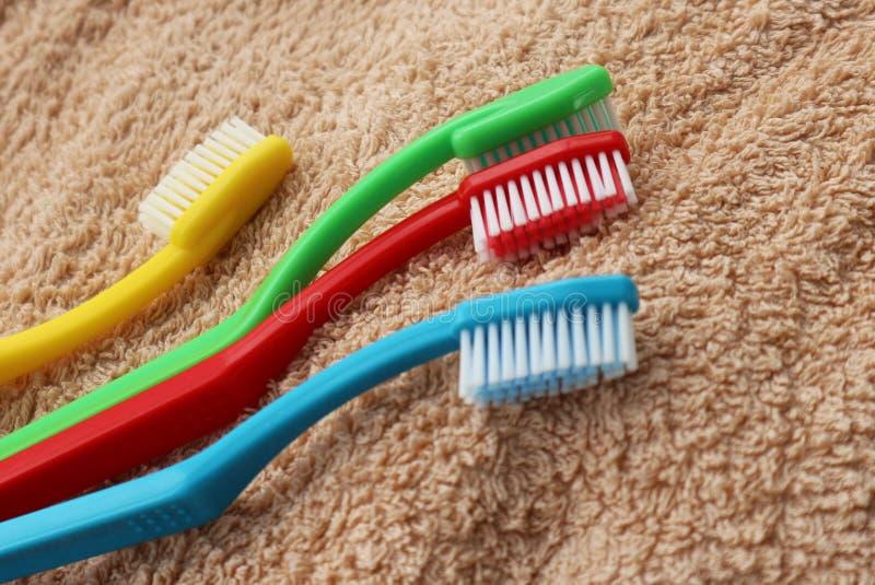 Vier kleurrijke tandenborstels die op beige handdoek liggen stock foto