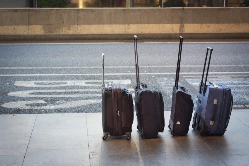 Vier koffers in een lijn bij de luchthaven stock foto's