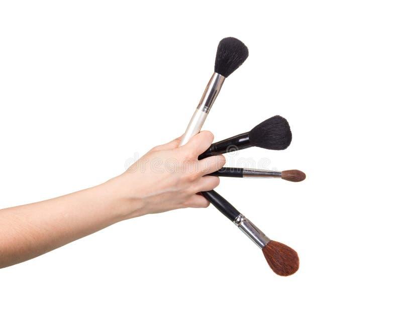 Vier kosmetische borstels in vrouwelijke die hand op witte backgroun wordt geïsoleerd stock afbeeldingen