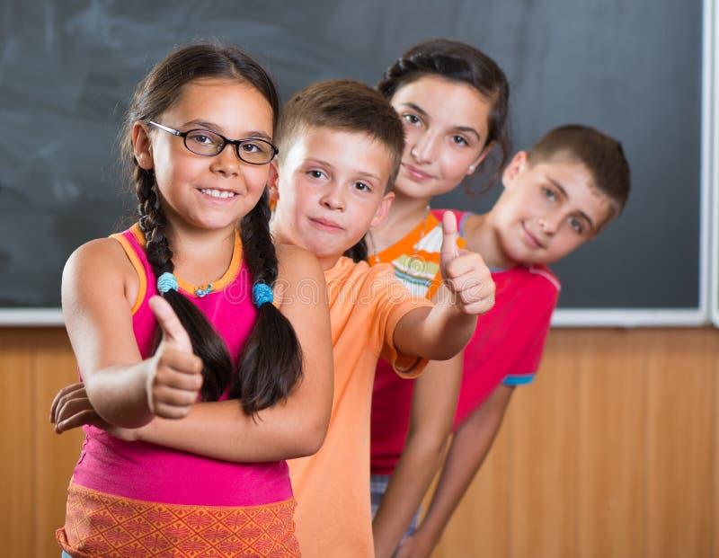 Vier lächelnde Schulkinder, die im Klassenzimmer stehen lizenzfreie stockfotografie
