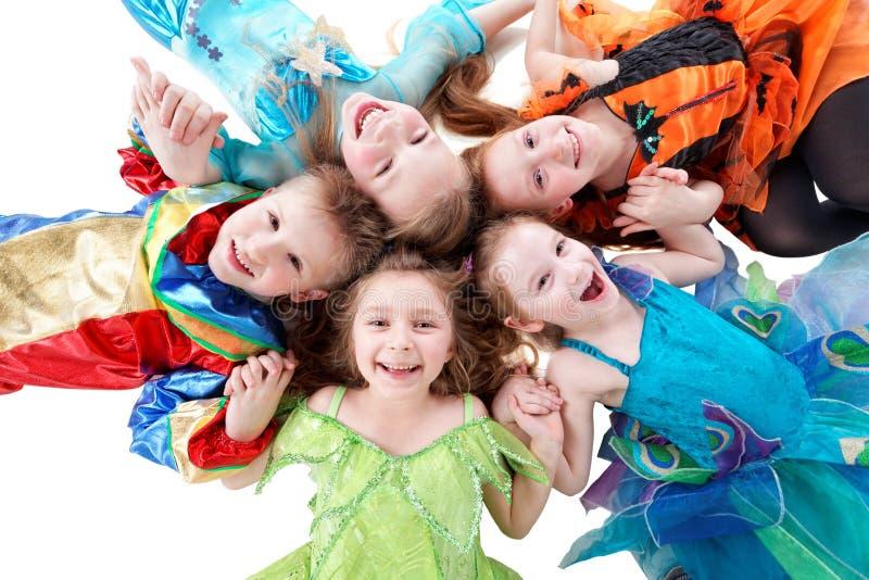 Vier lachende meisjes en één jongen, gekleed in kostuum, liggen royalty-vrije stock fotografie