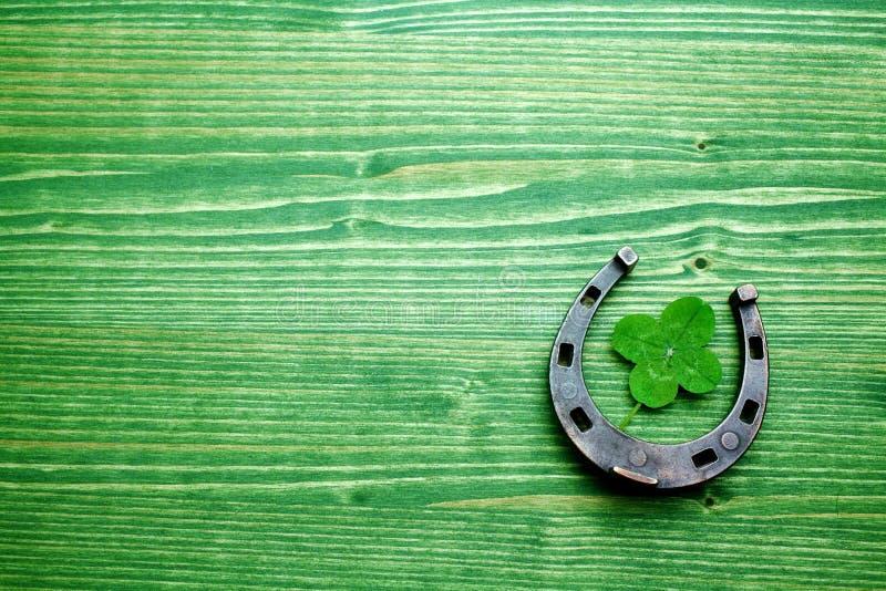 Vier-leaved klaver en een paardschoen op groene houten achtergrond St Patrick ` s dag stock foto's