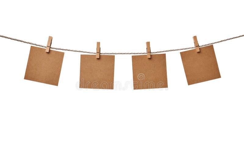 Vier leere Anmerkungen des Kraftpapiers, die am Seil lokalisiert auf weißem Hintergrund hängen lizenzfreie stockfotografie