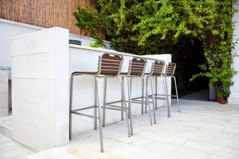 Vier leere Barhockerstühle mit hölzernen Sitzen und Metallfuß nahe einem weißen konkreten Stangenzähler lizenzfreies stockfoto