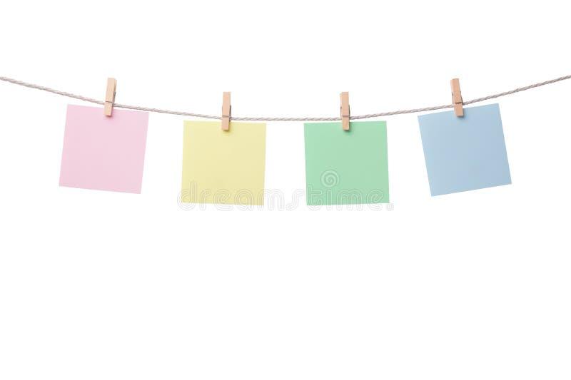 Vier leere Papieranmerkungen, die am Seil lokalisiert auf weißem Hintergrund hängen stockfotografie