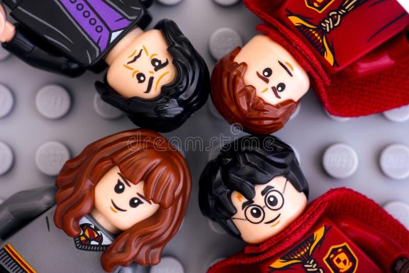 Vier Lego Harry Potter-minifigures - Harry Potter, Hermione Granger, Severus Snape en Oliver Wood op grijze achtergrond stock afbeelding