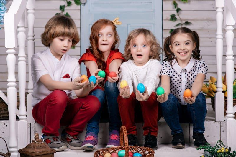 Vier leuke mooie babys zitten op de drempel houdend kleurrijke paaseieren Pasen stock foto's