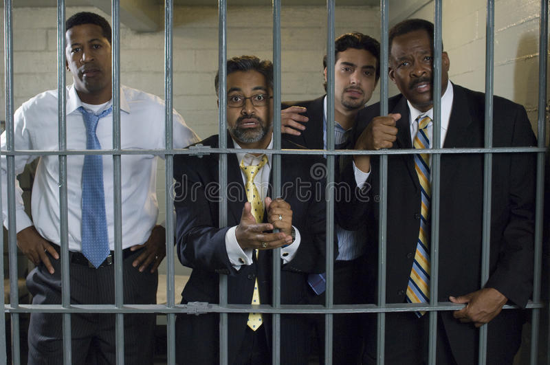 Vier Leute in der Gefängnis-Zelle lizenzfreie stockbilder