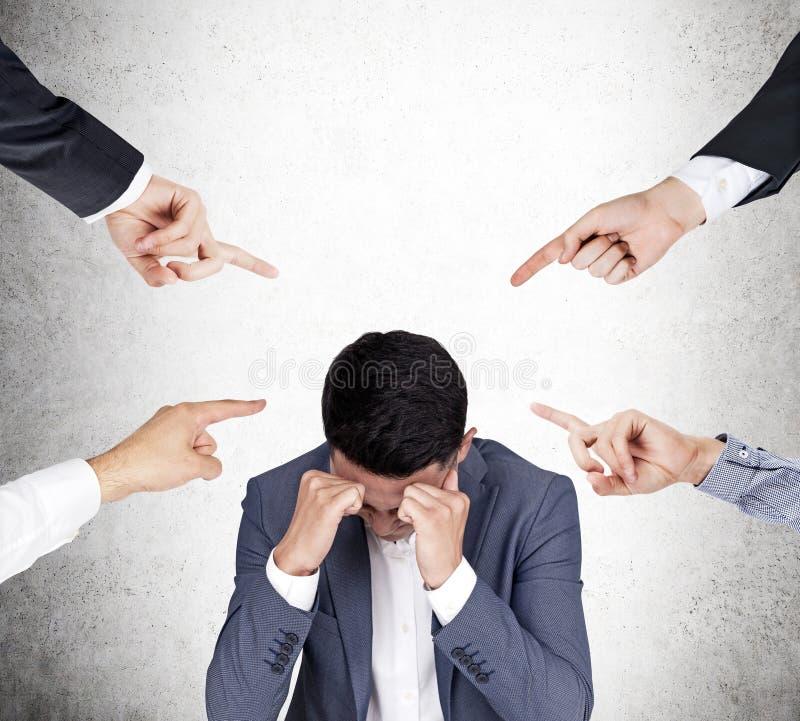 Vier Leute tadeln einen betonten asiatischen Geschäftsmann stockfoto