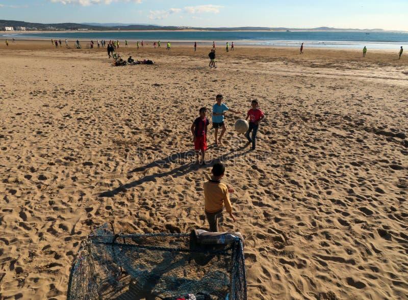 Vier lokale kinderen die strandvoetbal spelen stock fotografie