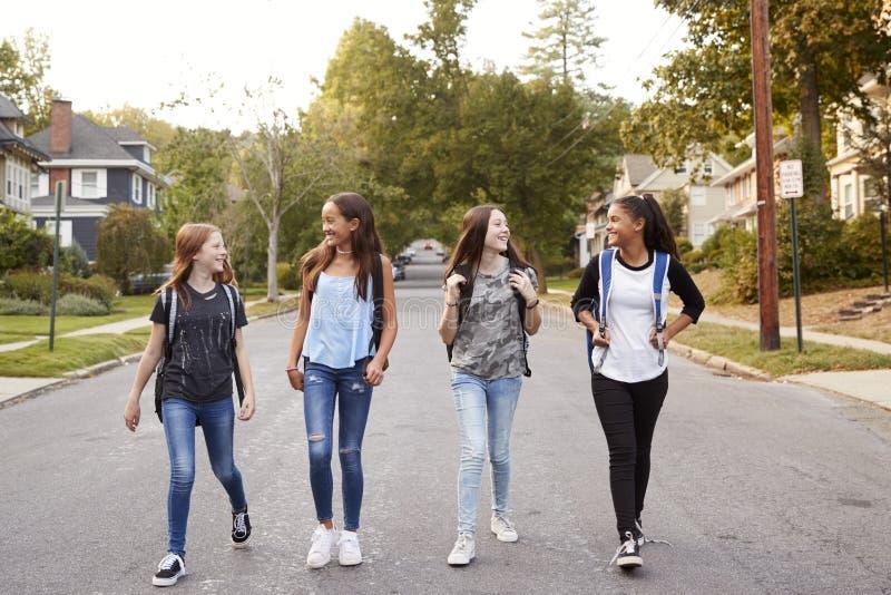 Vier Mädchen des jungen jugendlich, die in die Straße, in voller Länge gehen stockfotografie