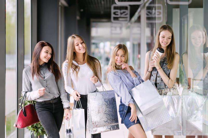 Vier Mädchen, die im Einkaufszentrum gehen stockfotos
