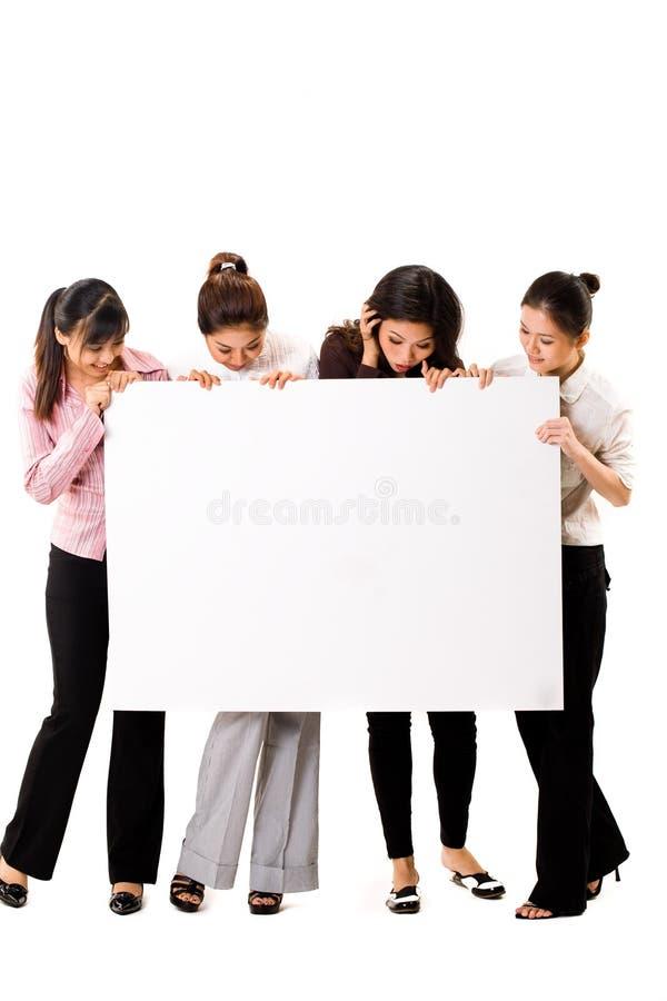Vier Mädchen mit einem weißen Zeichen lizenzfreie stockbilder