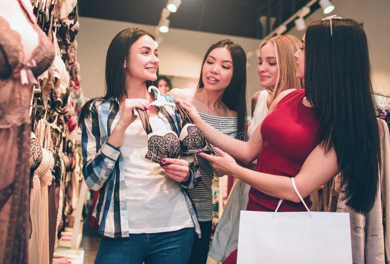Vier Mädchen sind im Unterwäscheshop Brunettemädchen hält BH, während ihre Freunde rät zu ihr geben Sie sind lizenzfreies stockfoto