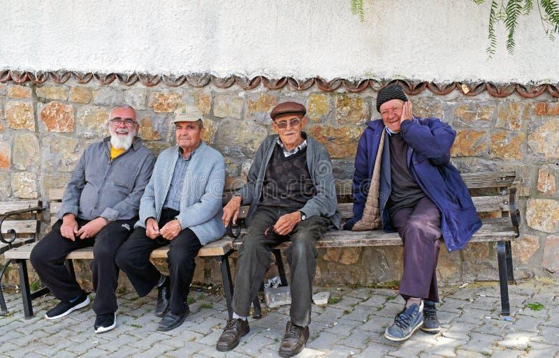 Vier Männer, die auf einer Bank in einem alten türkischen Dorf sitzen stockbilder