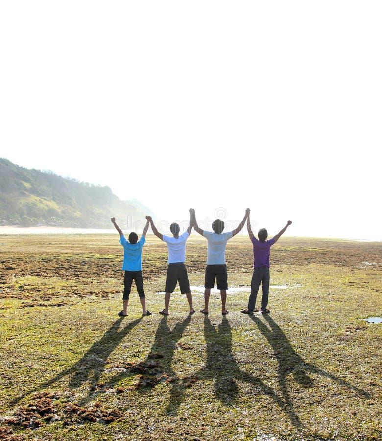 Vier Männer mit dem offenen Armgenießen lizenzfreies stockbild