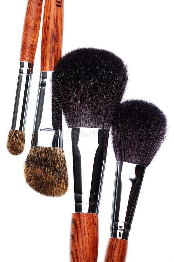 Vier make-upborstels op witte achtergrond stock afbeeldingen